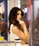Viva inteiramente Compra bonita agradável da jovem mulher ao andar através da alameda a menina olha em uma janela da loja imagem de stock