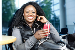 Vivacious African woman listening to music. On her MP3 player as she sits at an outdoor table at an open-air cafeteria Royalty Free Stock Images