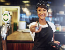 Vivacious bar tender handing back a card Royalty Free Stock Images