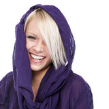 Vivacious beautiful blond. Woman wearing a hooded purple top laughing at the camera, head and shoulders portrait on white Royalty Free Stock Photography