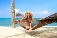Vivacious beautiful woman in hammock. Vivacious beautiful woman wearing a straw sunhat relaxing in a hammock tied to a palm tree on a tropical island resort Royalty Free Stock Images