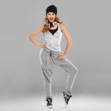 Vivacious beautiful young student. In casual track pants and a cap with a set of headphones aound her neck laughing at the camera Royalty Free Stock Images