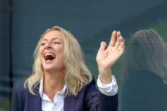 Vivacious blond kobieta śmia się falowanie zdjęcia stock