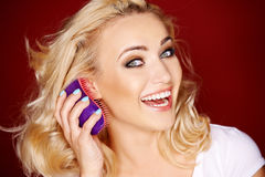 Vivacious blond woman brushing her hair Stock Photography