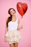 Vivacious brunette with a red heart balloon Stock Photos