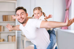 Vivacious father and daughter laying together. I believe I can fly. Close up of delighted vivacious father holding her daughter on the back and keeping hands royalty free stock images