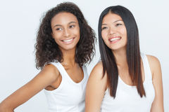 Vivacious friends keeping glance up. Evincing happiness. Pretty young women smiling and keeping glance up while standing together on white background Stock Images