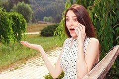 Vivacious girl holding mobile phone Stock Image