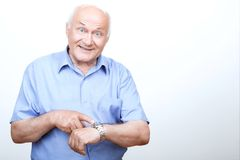 Vivacious grandfather pointing his wristwatch Stock Photo