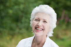 Vivacious laughing senior woman. Vivacious laughing grey haired senior woman outdoors in a lush green park, close up portrait Stock Images