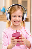 Vivacious little girl listening to music Royalty Free Stock Photography