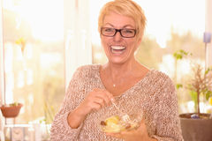 Vivacious middle-aged woman eating fruit salad. Vivacious attractive middle-aged woman wearing glasses eating a healthy bowl of fruit salad rich in vitamins Stock Images