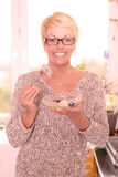 Vivacious middle-aged woman eating fruit salad. Vivacious attractive middle-aged woman wearing glasses eating a healthy bowl of fruit salad rich in vitamins Royalty Free Stock Images
