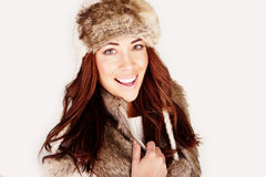 Vivacious Redhead In Winter Outfit. Vivacious redhead woman in winter outfit wearing fur hat and jacket, close-up head and shoulders, studio on white Stock Images