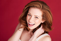 Vivacious Redhead Woman Laughing. Looking up in to the camera, studio on red Stock Image
