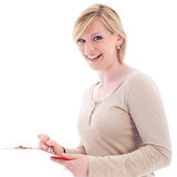 Vivacious secretary taking notes. Vivacious young blonde secretary laughing in amusement while taking notes on a handheld folder Royalty Free Stock Photography