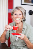 Vivacious senior woman drinking espresso Royalty Free Stock Photos