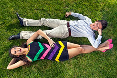 Vivacious teenagers lying head to toe. Vivacious teenage couple lying on their backs on lush green grass head to toe resting their arms on each others legs royalty free stock photos