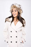 Vivacious Winter Beauty. A beautiful laughing vivacious lady dressed in winter coat and fur hat on white Royalty Free Stock Photography