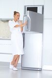 Vivacious woman in bathrobe and slippers. Vivacious woman in a white bathrobe and slippers standing laughing as she opens the freezer unit of her refrigerator Stock Image