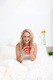 Vivacious woman with a cup of coffee. Vivacious young woman with lovely curly blonde hair enjoying a cup of coffee while sitting in bed Stock Photo