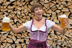 Vivacious woman in a dirndl with two beers Stock Photography