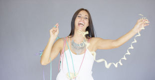 Vivacious woman at a fun New Year party. Vivacious elegant young woman at a fun New Year party smiling and laughing as she waves streamers in the air stock images