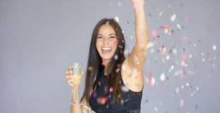 Vivacious woman having fun at a New Year party. Vivacious attractive  stylish young woman having fun at a New Year party cheering and raising a toast with a Stock Photo