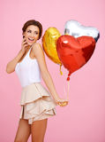 Vivacious woman with heart shaped balloons. Vivacious woman with colourful shiny red, gold and silver heart shaped party balloons on a pink background Stock Photography
