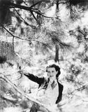Vivacious woman looking through the branches of a pine tree Stock Images