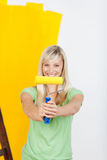 Vivacious woman painting with yellow paint Royalty Free Stock Image