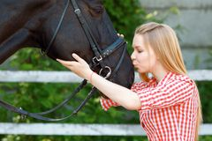 Vivacious young girl kissing the horse Royalty Free Stock Photography