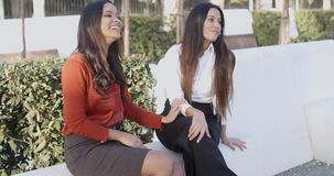 Vivacious young women sitting outdoors laughing stock video