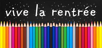 Vive la rentree meaning Back to school written on black chalkboard with colorful wooden pencils Stock Photo