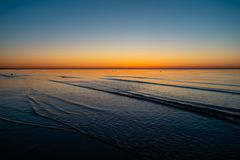 Vivid amazing sunset in Baltic States - Dusk in the sea with horizon illuminates by the sun royalty free stock photo