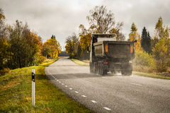 Autumn landscape of country-road with driving truck. Vivid autumn landscape with bright color trees and old truck driving on the country-road. Rainy, clouded Royalty Free Stock Image
