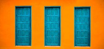 Vivid bright orange wall house facade with three blue-green closed doors on large empty orange wide wall texture background. Space in panorama banner format stock photography