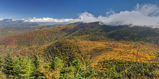 Vivid Catskill Mountain Autumn Panorama. Cornell and Wittenburg Mountains shrouded in misty clouds, seen from a lookout on Slide Mountain during peak Autumn Royalty Free Stock Photography