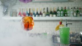 Vivid cocktails with fruits and plastic straws in glasses stand on table in smoke on background of bar interior. Vivid cocktails with fruits and plastic straws stock video