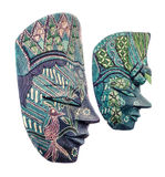 Vivid colored african masks, male and female, halloween mask close up, isolated Royalty Free Stock Photo