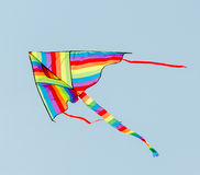 Vivid colored kite in the blue sky. Close up Stock Photos