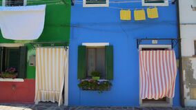 Vivid colorful houses painted in green and blue, nice flower pots on windows. Stock footage stock video