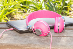 Vivid colorful pink headphones and laptop Royalty Free Stock Photography