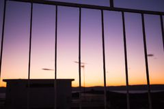 Vivid and colorful sunrise/sunset sky seen behind bars. Vivid and colorful sunrise/sunset sky seen behind bars Royalty Free Stock Photos