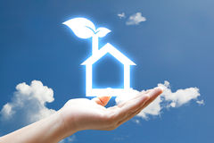 Vivid eco houes icon. Hand and vivid eco houes icon on sky Royalty Free Stock Image