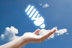 Vivid Eco lamp icon. Hand and vivid Eco lamp icon on sky Stock Photography