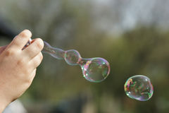 Vivid fantasies. Child producing soap bubbles with a bubble wand Stock Photography