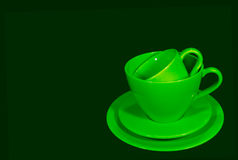Vivid green ceramic coffee cups with saucers on dark green background Stock Image