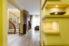 Vivid hall with lemon walls. And fitted shelves, opening to stairway Royalty Free Stock Photo