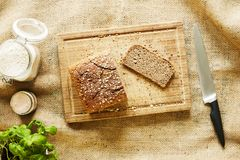 Vivid kitchen scenery slicing bread on wooden cutting board royalty free stock images